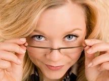 Bella signora bionda Looking Over i suoi vetri Fotografie Stock Libere da Diritti