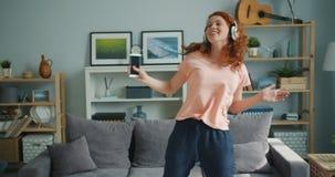 Bella signora che balla a casa le cuffie d'uso di canto che tengono smartphone archivi video