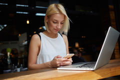 Bella signora che chiacchiera sullo Smart Phone mentre sedendosi alla tavola con il computer portatile nell'interno della barra d Immagini Stock