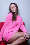 Bella signora che dura tricottando blusa rosa che si inginocchia sulla sedia rossa Fotografia Stock