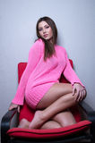 Bella signora che dura tricottando blusa rosa contro la parete della casa Fotografia Stock