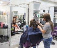 Bella signora che fa capelli nel salone Parrucchiere che fa taglio di capelli nel salone di lavoro di parrucchiere La Russia St P fotografie stock