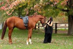 Bella signora che si leva in piedi con il suo cavallo in autunno immagine stock libera da diritti