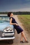 Bella signora che si leva in piedi vicino alla retro automobile fotografie stock libere da diritti