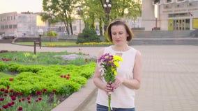 Bella signora che tiene un mazzo di bei fiori Mano femminile che tocca i bei fiori Godere della natura stock footage