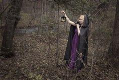 Bella signora con la lanterna ha perso nella foresta di autunno Fotografia Stock