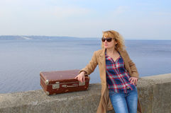 Bella signora con la valigia d'annata sulla spiaggia Fotografia Stock
