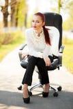 Bella signora di affari che si siede sulla sedia dell'ufficio Immagini Stock