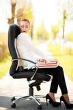 Bella signora di affari dei rosso-capelli che si siede sulla sedia dell'ufficio con i libri Immagini Stock