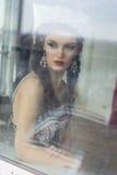Bella signora guarda attraverso la finestra Immagine Stock Libera da Diritti