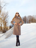 Bella signora ha vestito un cappotto e gli occhiali da sole immagine stock