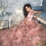 Bella signora nelle alte mode splendide si veste sul sofà Fotografie Stock