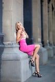 Bella signora pende contro le colonne in un vestito Immagine Stock