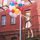 Bella signora in retro attrezzatura che tiene un mazzo di betwe dei palloni Fotografie Stock Libere da Diritti
