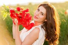 Bella signora sopra il cielo ed il tramonto nel campo che tiene un mazzo dei papaveri, sorridente Fotografia Stock