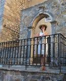 Bella signora in un cappello di paglia sui precedenti dell'arco antico openwork fotografia stock libera da diritti