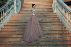 Bella signora in vestito lussuoso dalla sala da ballo che cammina sulle scale del suo palazzo fotografie stock libere da diritti