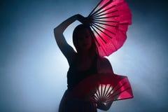 Bella siluetta di una ragazza che balla elegante in fumo e nebbia Fotografie Stock Libere da Diritti