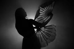 Bella siluetta di una ragazza che balla elegante in fumo e nebbia immagine stock