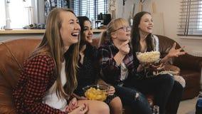 Bella soap opera dell'orologio dei girlriends sulla TV Le ragazze sorridono e ridono godendo del movimento lento romantico emozio Fotografie Stock