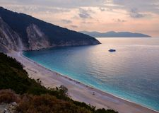 Bella spiaggia di Myrtos con acqua del turchese sul tramonto sull'isola di Kefalonia nel Mar Ionio in Grecia fotografia stock libera da diritti