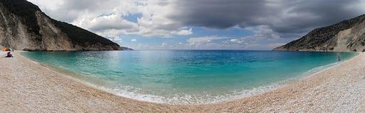 Bella spiaggia di Myrtos di vista panoramica con chiara acqua del turchese un giorno soleggiato nel Mar Ionio sull'isola di Kefal fotografia stock