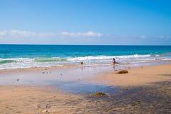 Bella spiaggia piana con due bambini che giocano nell'oceano blu fotografia stock