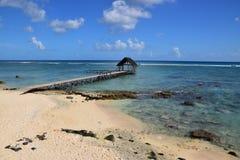 Bella spiaggia rocciosa con la capanna di legno del pilastro del molo Immagine Stock