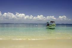 Bella spiaggia tropicale all'isola di Kapas, Malesia barca turistica ancorata con il fondo del cielo blu e il wate blu cristallin immagini stock