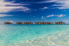 Bella spiaggia tropicale con i bungalow dell'acqua in Maldive Immagine Stock