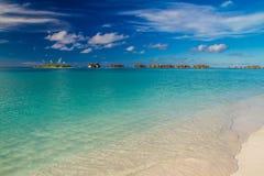 Bella spiaggia tropicale con i bungalow dell'acqua in Maldive Immagini Stock
