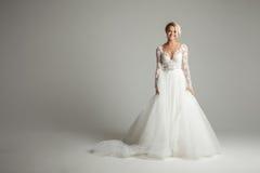 Bella sposa attraente in vestito da sposa con la gonna lunga lunga, il fondo bianco, il ballo ed il sorriso Fotografia Stock