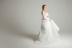 Bella sposa attraente in vestito da sposa con la gonna lunga lunga, il fondo bianco, il ballo ed il sorriso Fotografie Stock