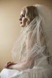 Bella sposa bionda che si siede sopra il fondo di legno giorno Immagini Stock Libere da Diritti