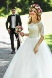 Bella sposa bionda elegante nella camminata bianca dello sposo e del vestito Fotografia Stock