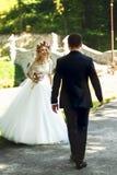 Bella sposa bionda elegante nella camminata bianca dello sposo e del vestito Fotografie Stock Libere da Diritti