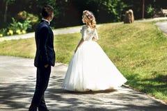 Bella sposa bionda elegante nella camminata bianca dello sposo e del vestito Immagini Stock Libere da Diritti