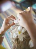 Bella, sposa bionda sveglia che fa capelli con i fiori prima del weddi Immagini Stock