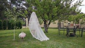 Bella sposa bionda in un vestito da sposa lungo lussuoso che cammina nel giardino verde Mattina della sposa Giorno delle nozze video d archivio