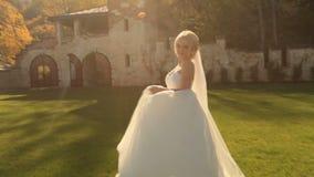 Bella sposa bionda in vestito bianco che posa alla macchina fotografica sul cortile medievale del castello video d archivio