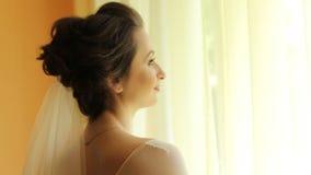Bella sposa castana che sta vicino alla finestra video d archivio