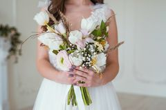 Bella sposa castana con un mazzo del fiore nella stanza vicino ad una parete bianca fotografia stock
