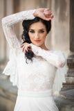 Bella sposa castana innocente in vestito bianco che posa vicino a CHU immagini stock libere da diritti