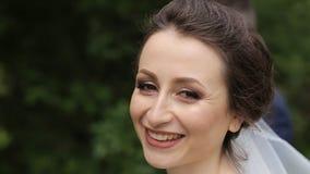 Bella sposa che sorride alla macchina fotografica nel parco un giorno soleggiato video d archivio