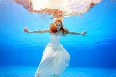 Bella sposa con capelli rossi che nuota underwater nello stagno al tramonto, armi stese ai lati Fotografie Stock Libere da Diritti