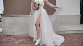 Bella sposa con le gambe lunghe in un vestito bianco primo piano delle sue gambe lunghe archivi video