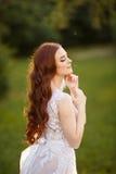 Bella sposa della testarossa che gioca con i suoi capelli fotografia stock
