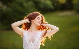 Bella sposa della testarossa che gioca con i suoi capelli fotografia stock libera da diritti