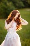 Bella sposa della testarossa in vestito da sposa fantastico in giardino di fioritura fotografie stock