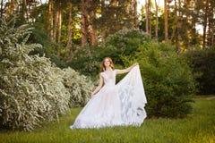 Bella sposa della testarossa in vestito da sposa fantastico in giardino di fioritura immagine stock